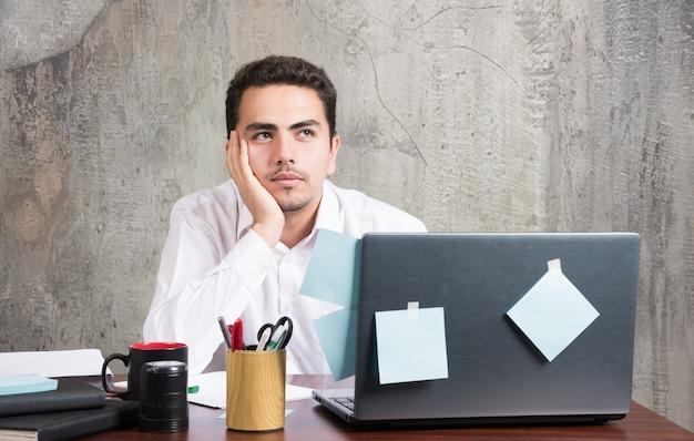 Бизнесмен, интенсивно глядя на ноутбук за офисным столом.