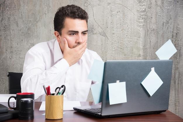 Бизнесмен, глядя на ноутбук, держа рот за офисный стол.