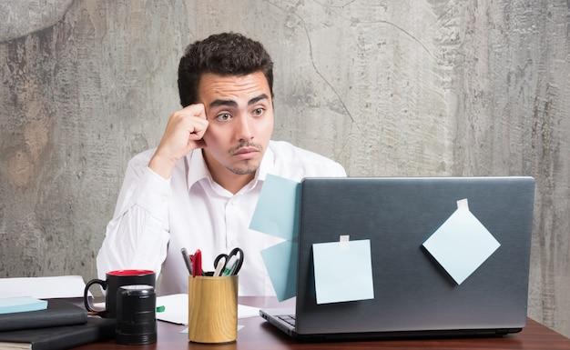 Бизнесмен, глядя на ноутбук с удивленным выражением лица за офисным столом.