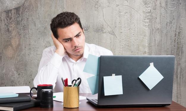 Бизнесмен, глядя на ноутбук с усталым выражением лица за офисным столом.