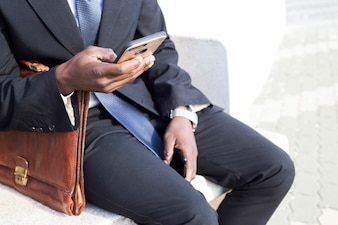Businessman looking at smartphone on bench