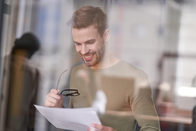 Бизнесмен, глядя на заявление с радостью и улыбкой