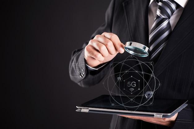 돋보기 5g 개념으로 태블릿을 보고 있는 사업가