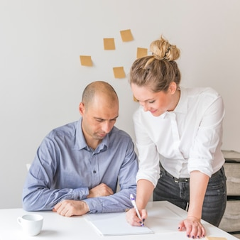 Businessman looking at businesswoman writing on notepad