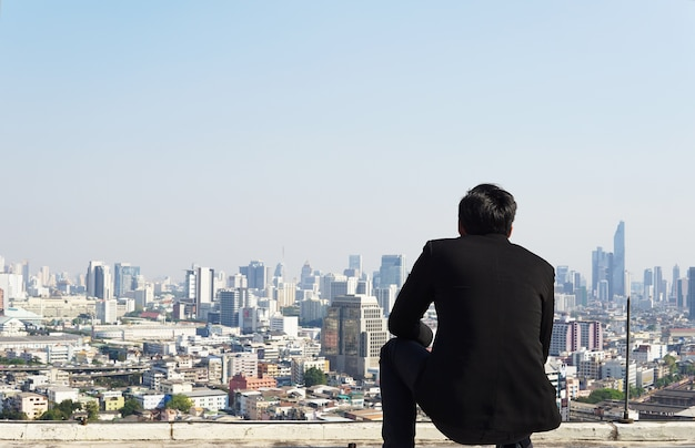 Businessman looking city to the future on rooftop