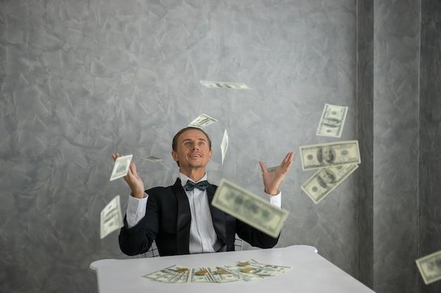 Businessman looking at dollar bills falling around him