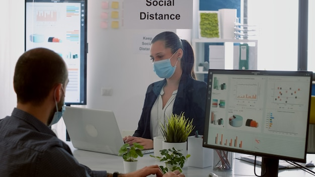 Businessman looking at financial graphs on computer display while talking with coworker sitting in company office. colleagues with face masks keeping social distancing to prevent covid19 disease