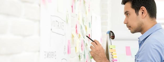 Бизнесмен ищет информацию из липких заметок на стене