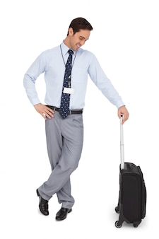 Businessman looking at his suitcase and smiling