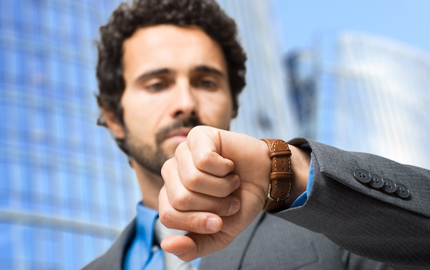 Businessman looking at his watch in front of his office. focus on the wrist