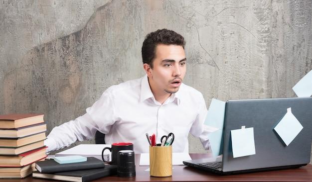 Бизнесмен ищет ноутбук с потрясенным выражением лица за офисным столом.