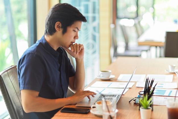 財務報告書、事務用品、作業スペースでコーヒーカップとラップトップを探しているビジネスマン