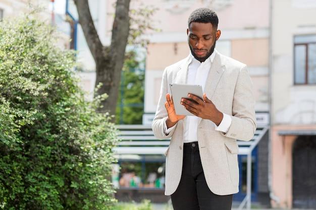 Бизнесмен, глядя на планшет