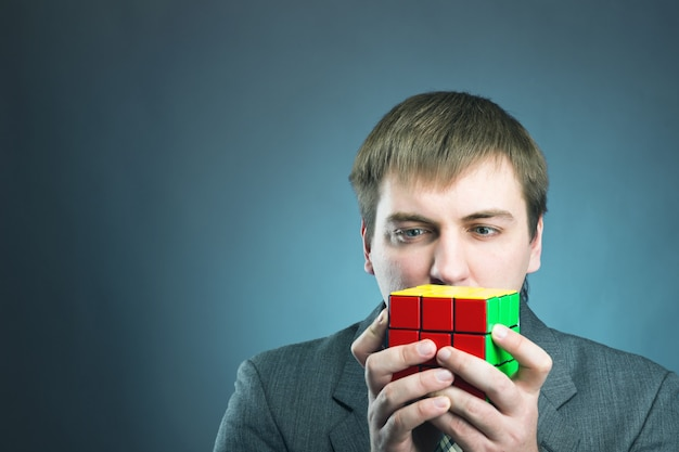 Businessman looking at  rubik cube in his hands