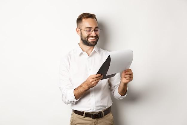 Бизнесмен, удовлетворенный документами, читая отчет и улыбаясь, стоя
