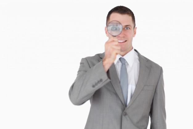 Бизнесмен, глядя через увеличительное стекло