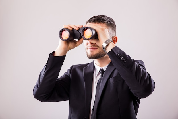 Businessman looking through binoculars isolated on white wall