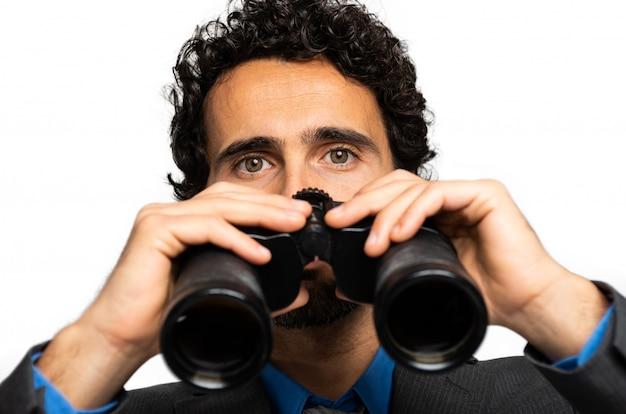 Businessman looking through binoculars isolated on white