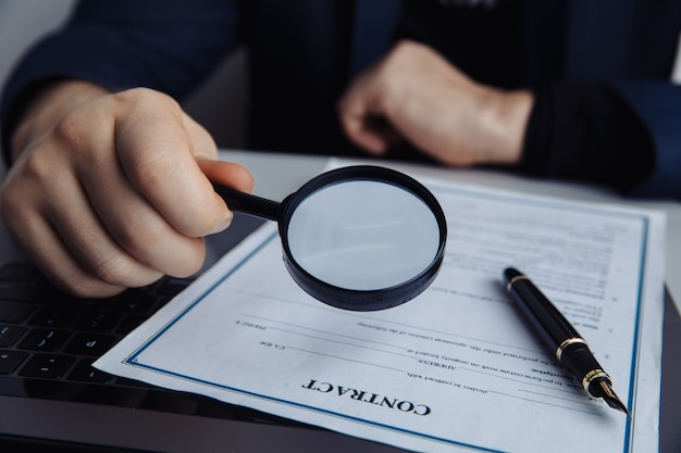 Businessman looking through magnifying glass to a contract.
