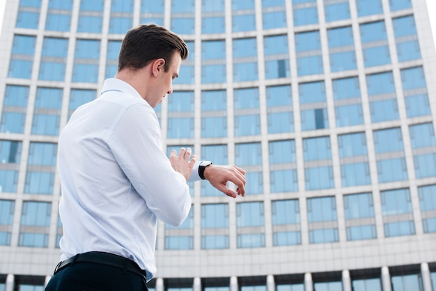 Businessman looking at watch near building