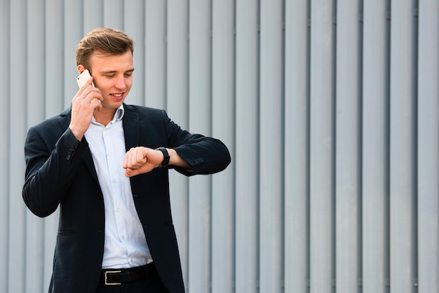 Businessman looking at watch while on the phone