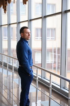 Businessman looking at the window in a huge business center.