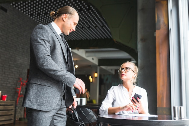 Businessman looking at woman holding mobile phone sitting in caf�