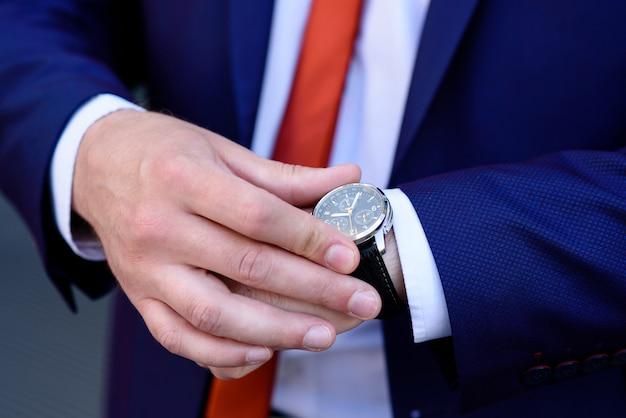 Бизнесмен смотрит на часы.