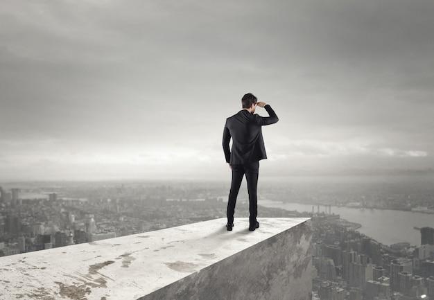 사업가 도시 위의 지붕에서 도시를 본다