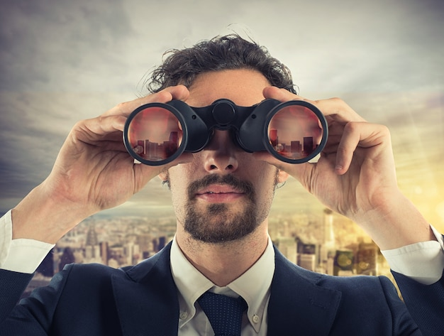 ビジネスマンは双眼鏡で屋上から街を見る