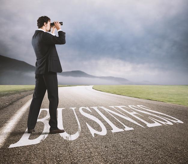 ビジネスマンは、ビジネスの道に双眼鏡で経済の未来を見ています