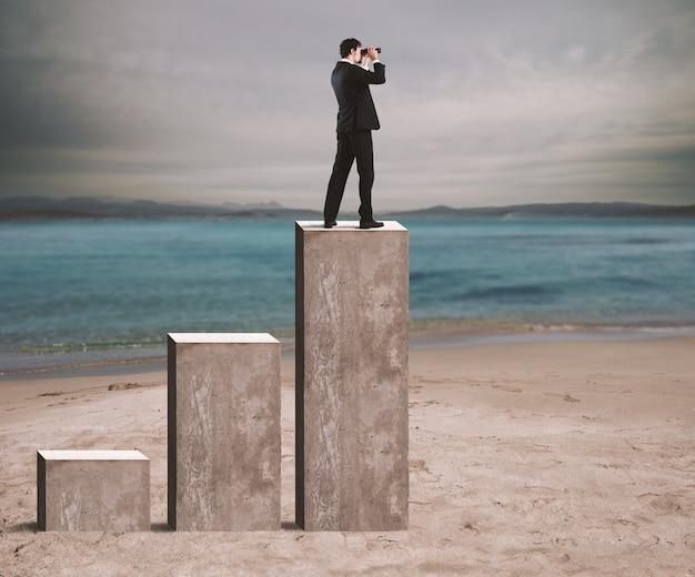 Бизнесмен смотрит на экономическое будущее в бинокль над статистикой