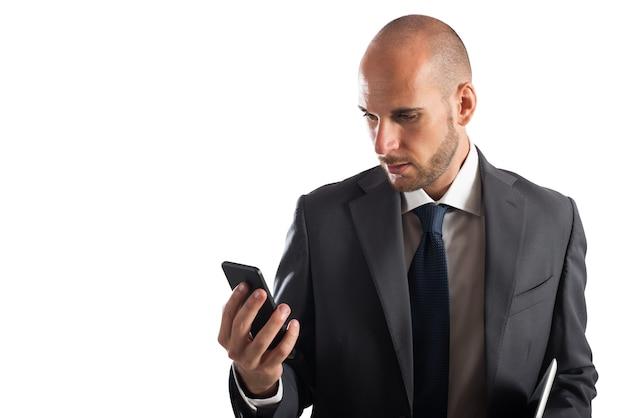ビジネスマンは彼の携帯電話の画面を見ます