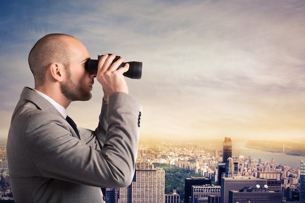 Businessman looks at the city landscape with binoculars