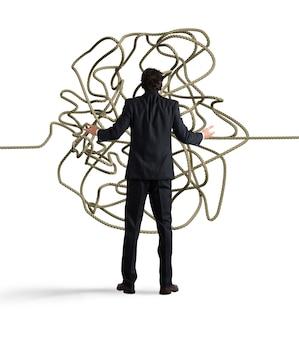 ビジネスマンはロープのもつれを混乱させているように見えます。ソリューションの概念を見つける