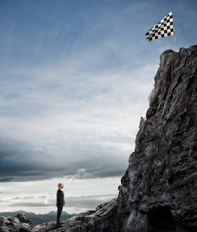 Businessman looks at a flag on mountain peak. business concept of businessman overcome the problems