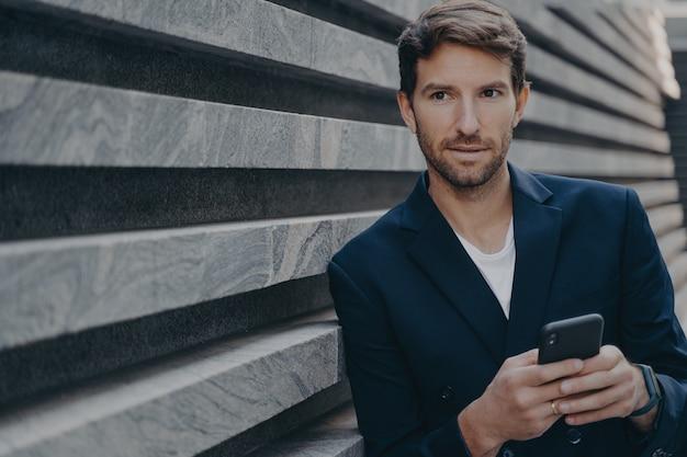 Businessman looks thoughtfully into distance uses smartphone thinks about future career success
