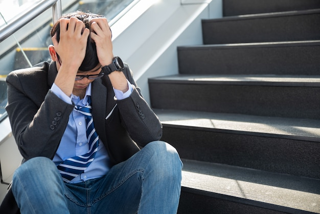Businessman lost in depression crying sitting on ground street stairs