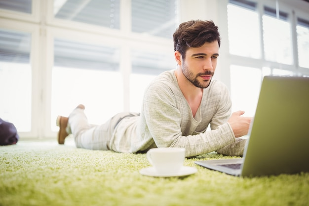 Businessman lying on carpet while using laptop in office