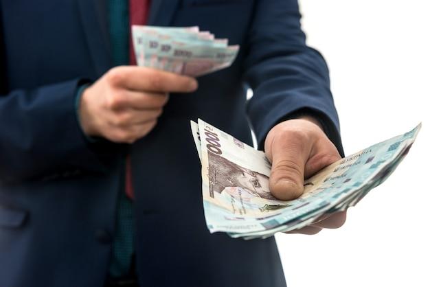 ビジネスマンは莫大な利益を上げ、たくさんのお金を見せました。スーツを着た男がウクライナの新しい銀行のパックを持っています。 1000グリブナ