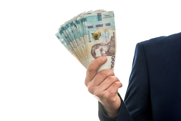 Бизнесмен получил огромную прибыль, показав большие деньги. мужчина в костюме держит пачку новых банктонов украины. 1000 гривен