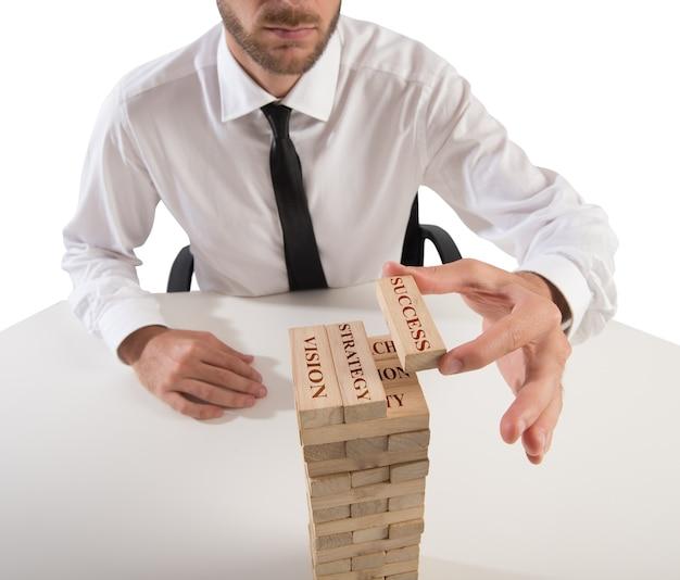 ビジネスマンは木のブロックで建物を作る