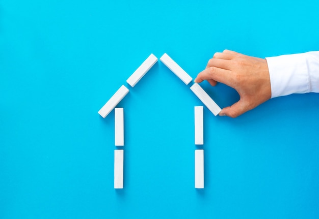 Бизнесмен, делая дом из деревянных блоков