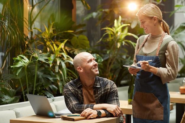 カフェのテーブルでノートパソコンを操作しながらウェイターに注文するビジネスマン