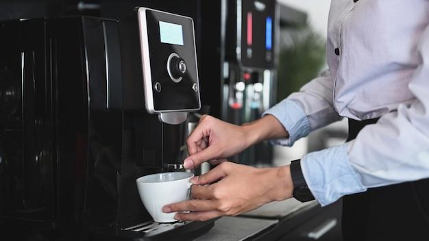 Бизнесмен делает кофе из кофеварки в офисе.