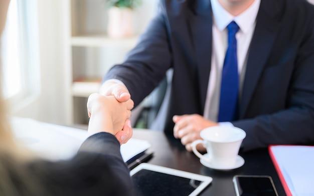 Бизнесмен делает рукопожатие в офисной комнате