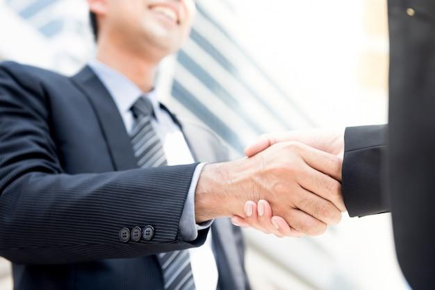 Бизнесмен делает рукопожатие с бизнес-леди