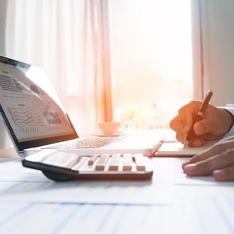 オフィスの窓の端で紙にノートを作るビジネスマン