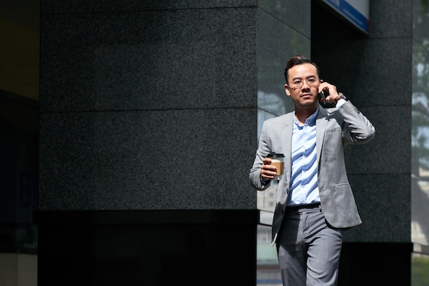 Businessman making a phone call on the move outdoors