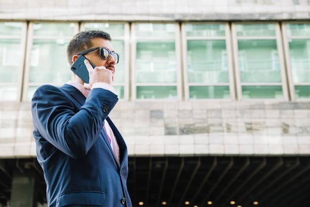 Uomo d'affari che fa telefonata nell'ambiente urbano